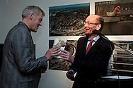 Hugo ter Avest van het Hannemahuis te Harlingen biedt de nieuwe rondwandelgids 'Koppen boven water' aan aan Harry Boon, dagelijks bestuurslid van Wetterskiip Fryslân. Dit gebeurde tijdens de opening van de tentoonstelling 'Koppen boven water - 500 jaar bescherming tegen het water'.