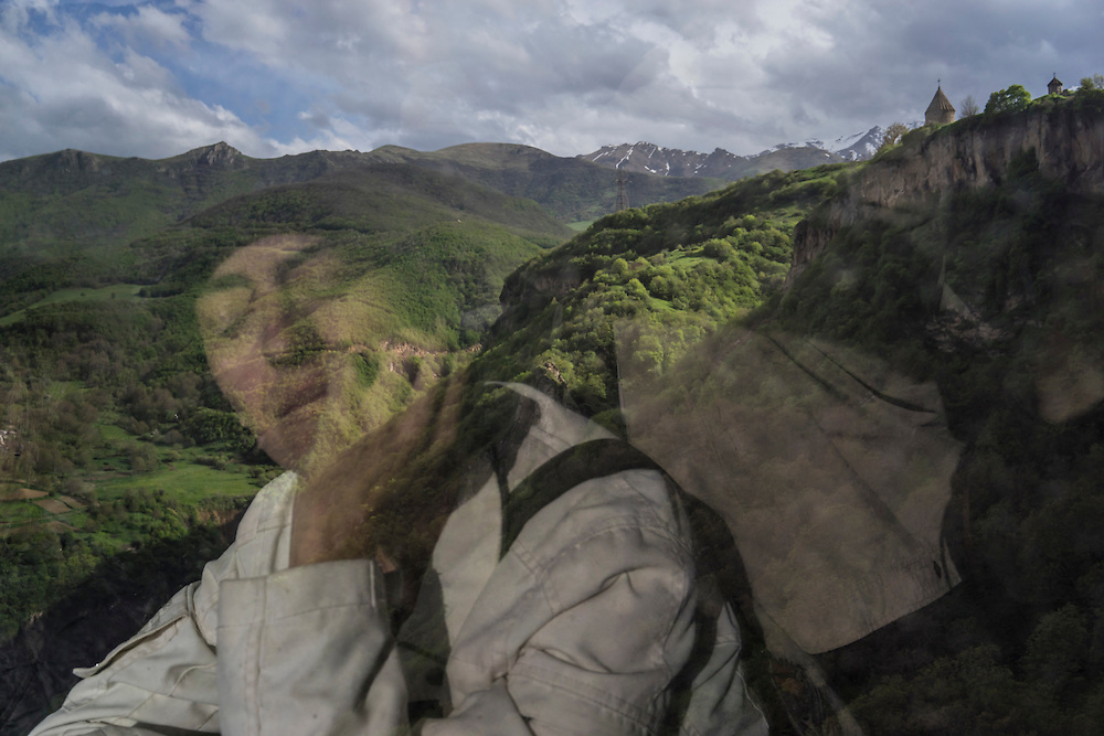 Monica Ellena is reflected in the window of the Wings of Tatev aerial tramway, with the Tatev Monastery visible in the background, on Saturday, May 7, 2016 in Tatev, Armenia.