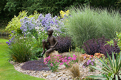 Summer border with statue 'Boy on the Rock' by Jane Hogben set on a boulder in a gravel bed