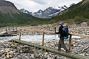 A hiker crosses footbridges. Mount Robson Provincial Park, British Columbia, Canada is part of the Canadian Rocky Mountain Parks World Heritage Site declared by UNESCO in 1984.