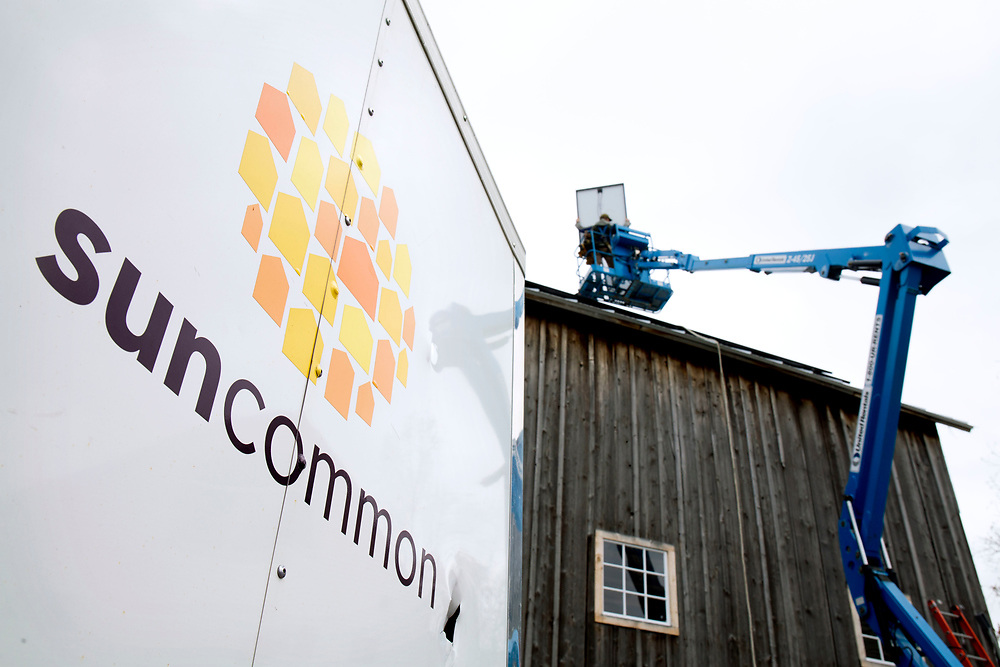 Peck Electric subcontractors install 60 SunCommon solar panels on a 150-year-old barn at 4 Corners Farm in Newbury, Vt., on May 9, 2017. With the panels feeding back into the electrical grid, farmer Bob Gray said he's looking forward to a lower monthly power bill. (Photo by Geoff Hansen)