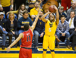 Mar 2, 2016; Morgantown, WV, USA; West Virginia Mountaineers guard Jaysean Paige (5) shoots a three pointer over Texas Tech Red Raiders forward Zach Smith (11) during the first half at the WVU Coliseum. Mandatory Credit: Ben Queen-USA TODAY Sports