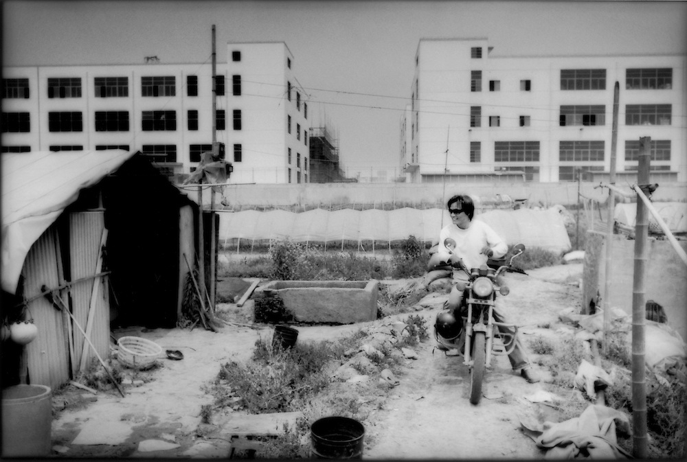 Motorcycle rider pauses in front of tents used by farmers for storing tools and making daytime meals while the future of industry landuse hovers in the background, west of Hongqiao Airport, Shanghai, China.  Land surrounding this agricultural area has either been converted to industrial and residential development or has been prepared for the conversion.