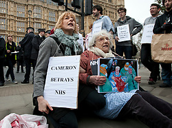 **Retransmission with name of protestor** © licensed to London News Pictures. London, UK 27/02/2012. A group of NHS protesters including 81 year-old Shirley Mugraff (right) blocking Arbingdon Street, next to the Houses of the Parliament as they protest the government's NHS reform. Photo credit: Tolga Akmen/LNP