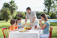 Family with three children (6-11) sitting at breakfast table outdoors