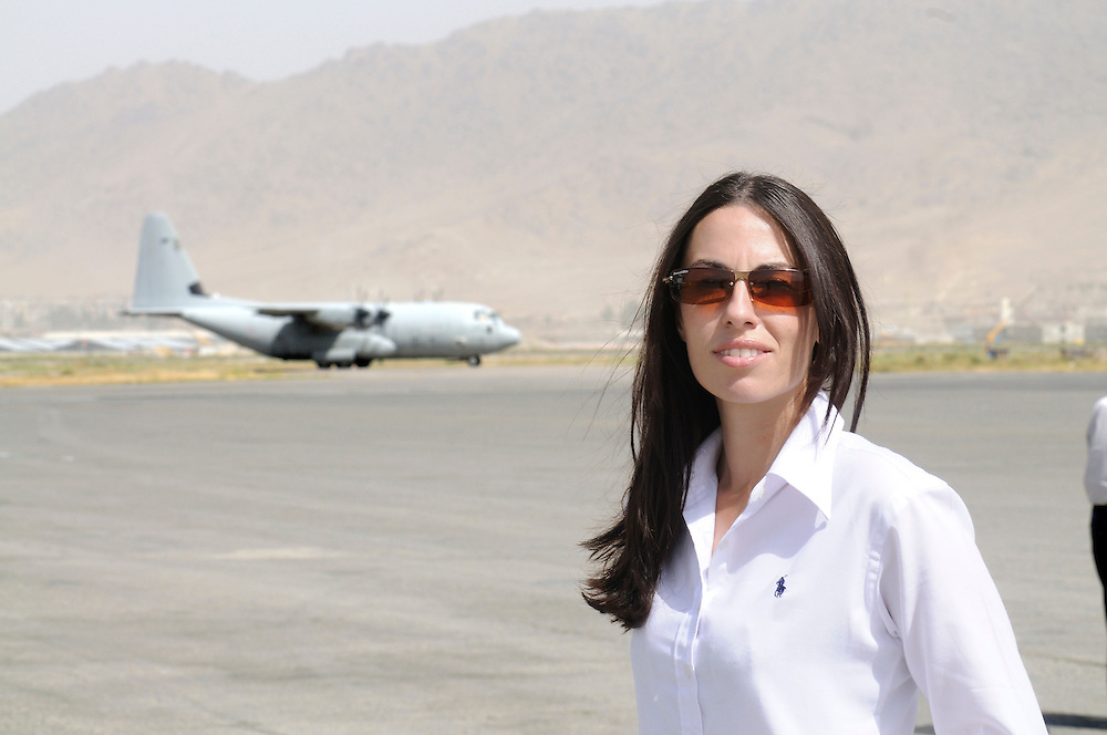 "Pilot, Danielle Aitchison, stands on the tarmac at Kabul International Airport while a US Airforce C-130 taxies for takeoff.  Danielle flies in Afghanistan for The United Nations Humanitarian Air Service (UNHAS).   ...When asked about flying in a war zone, she says,  ""I'm just a normal average female.  My job is maybe a little different to some, but I have the same feminine side as other women.  I don't have any trouble going back to New Zealand relating to people.  I'm just a regular chick.""."