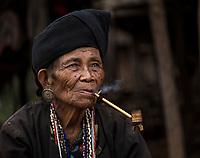 KYAING TONG, MYANMAR - CIRCA DECEMBER 2017: Portrait of elder woman of the Wan Sai Akha Village in Kyaing Tong smoking.