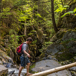 A man crosses a log next to Screw Auger Falls on Gulf Hagas Brook. Appalachian Trail. Maine's 100 Mile Wilderness.