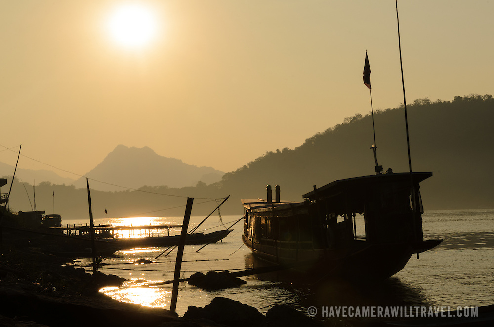 A wooden covered sampan is silhouetted against the setting sun on the banks of the Mekong River near Luang Prabang in central Laos.