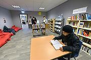 Nederland, Nijmegen, 30-11-2015Twee syrische vluchtelingen in hun pop-up bibliotheek van de Openbare Bibliotheek Gelderland Zuid in tentenkamp, noodopvang, Heumensoord. Asielzoekers mogen nog geen taalles krijgen, maar kunnen zo wel uit boeken leren.FOTO: FLIP FRANSSEN/ HH