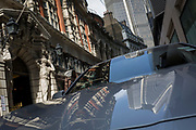 Towers and architecture of Drapers' Hall including the Atlantes figures by sculptor H.A. Pegram, reflected in the bonnet of a car parked in Throgmorton Street, on 17th Juy 2017, in the City of London, England. The Drapers' Company is a Livery Company in the City of London whose roots go back to the 13th century, when as its name indicates, it was involved in the drapery trade. While it is no longer involved in the trade, the Company has evolved acquiring a new relevance. Its main role today is to be the trustee of the charitable trusts that have been left in its care over the centuries. The Company also manages a thriving hospitality business. The first Drapers' Hall was built in the 15th century in St Swithin's Lane.  It bought a Hall on the present site in Throgmorton Street in 1543 from King Henry VIII for £1,200 (about £350,000 in today's money). The Hall that the Company purchased from King Henry VIII in 1543 had been the private residence of Thomas Cromwell, Earl of Essex until his execution in 1540, when it was confiscated by the Crown.