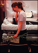 May 1999  A young woman carrying Columbine flowers walks by the casket of Isaiah Shoels, one of the Columbine victims. He was the only African American killed during the shooting. Inside the casket his parents had placed his high school diploma which he was to have received at the end of the school year at graduation. (Essdras M Suarez/ Rocky Mountain News©)