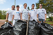 Rebuilding Together and volunteers clear vegetation and debris from near a park