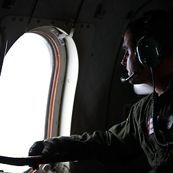 Coast Guard Avionics Electrical Technician Brandon Hotard looks out from a  window of an HC-144A Coast Guard airplane during a flight over the Deepwater Horizon oil spill in the Gulf of Mexico near the coast of Louisiana, U.S., on Wednesday, June 2, 2010. BP Plc has given up trying to plug its leaking well in the Gulf of Mexico any sooner than August, laying out a series of steps to pipe the oil to the surface and ship it ashore for refining, said Thad Allen, the U.S. government's national commander for the incident. Photographer: Derick E. Hingle