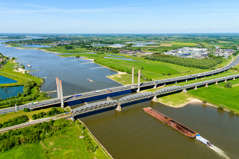 Nederland, Gelderland, Zaltbommel, 13-05-2019; bruggen over de rivier de Waal bij Zaltbommel. Naast de spoorbrug, spoorlijn Utrecht - Den Bosch, de Martinus Nijhofbrug voor autoverkeer op rijksweg A2. Intercity trein verlaat de spoorbrug.<br /> Bridges over the River Waal. Railway bridge, railway line Utrecht - Den Bosch and the Martinus Nijhof bridge, motorway A2.<br /> aerial photo (additional fee required); luchtfoto (toeslag op standard tarieven); copyright foto/photo Siebe Swart