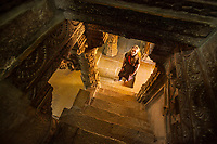A female tourist poses for a picture at the base of some stairs in a Jain Temple within the Jaisalmer Fort, Jaisalmer, Rajasthan, India.