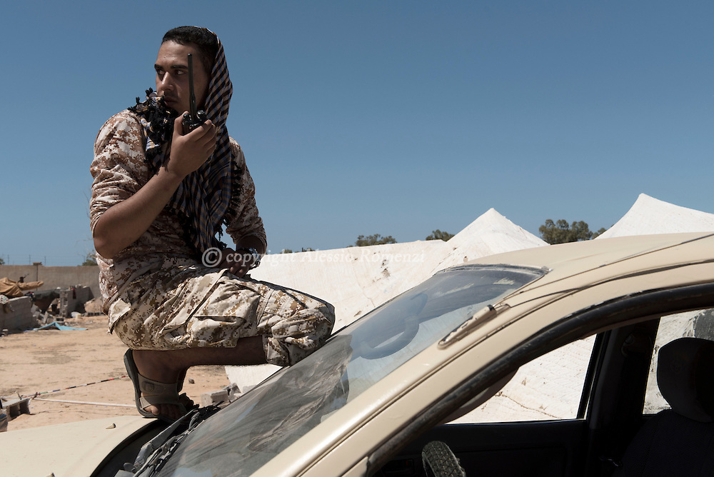 Libya: A fighter sympathising with Libya's Government of National Accord's (GNA) talks on the walkie talkie on the frontline with ISIS positions in Ouagadougou conference center area in Sirte. Alessio Romenzi