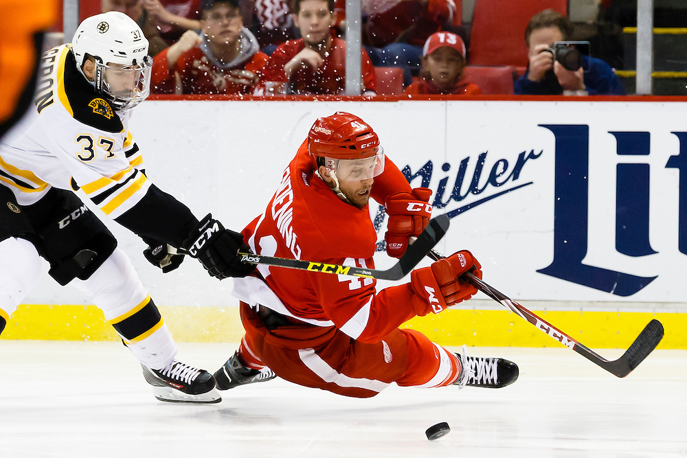 Apr 2, 2015; Detroit, MI, USA; Boston Bruins center Patrice Bergeron (37) trips Detroit Red Wings right wing Luke Glendening (41) in the third period at Joe Louis Arena. Boston won 3-2. Mandatory Credit: Rick Osentoski-USA TODAY Sports