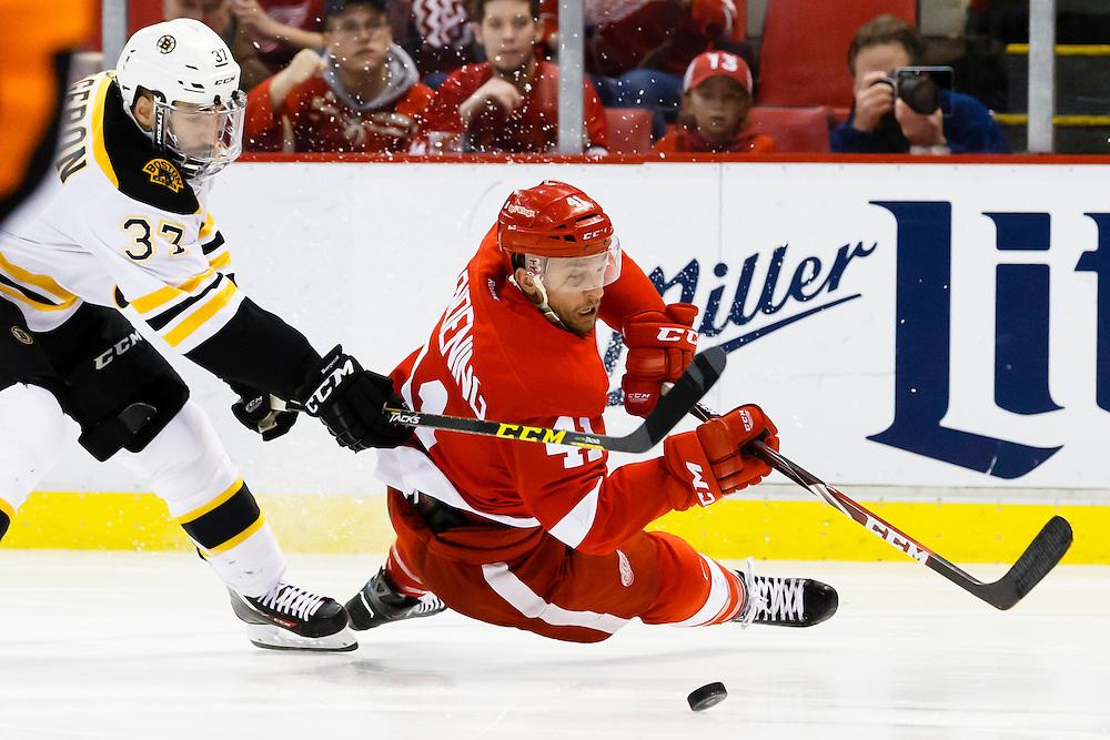 Apr 2, 2015; Detroit, MI, USA; Boston Bruins center Patrice Bergeron (37) trips Detroit Red Wings right wing Luke Glendening (41) in the third period at Joe Louis Arena. Boston won 3-2. Mandatory Credit: Rick Osentoski-USA TODAY Sports