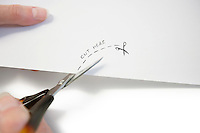 Hand using scissors to cut paper