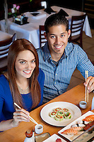 Portrait of a happy couple eating sushi with chopsticks in Japanese restaurant
