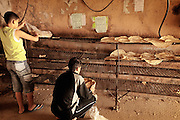 Two boys place bread on racks to dry in a rural area in Syria