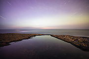 Long exposure nightshot, with view to infinity. Startrails reflecting into water | Nattbilde med lang eksponering med utsikt til evigheita. Stjernespor som reflekterer i sjøen.