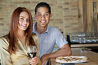 Portrait of happy young couple sitting at counter with pizza and wine