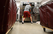 Equipment managers work in the Mal Moore Athletic Facility to get the University of Alabama football team ready for the trip to Baton Rouge to face LSU.  Student manager Clint Bradford stuff a washer full of practice uniforms for washing.  Photo by Gary Cosby Jr.