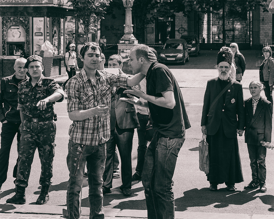 Ukraine - Kyiv - 09 May 2014 - The man in black t-shirt pretend that he got beat-up by soldiers on Maidan place in Kiev. The soldier on the left ask me to stop shooting photos.