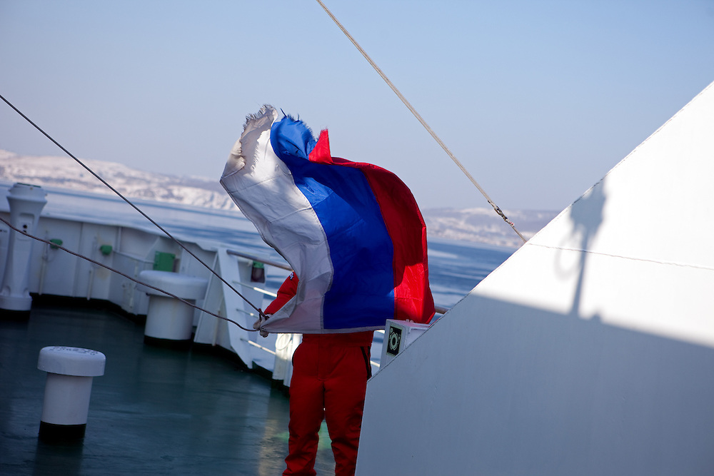 "Employee of the ""Eastern Dream"" ferry running up the russian flag during arrival to the sea port of Vladivostok in Russia. Vladivostok, Russian Federation, Russia, RUS, 12.01.2010."