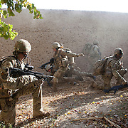 A soldier from 3 SCOTS (The Black Watch) runs out from a rising cloud of dust and smoke after an IED explosion just inside the doorway of a compound . Private Stephen Bainbridge, aged 25, from Kirkcaldy was gravely wounded in the blast which traumatically amputated his right leg and damaged his right so badly that it too later had to be amputated. His life was saved by the swift actions of Cpl John Goodie (21) a medic with 1 PWRR (The Princess of Wales's Royal Regiment) who applied tourniquets and first field dressings to get the bleeding under control. Private Chis Watson (21) also assisted in the treatment whilst reassuring the casualty and keeping him alert and responsive.  Once he had been stabilized the men CASEVAC'd Private Bainbridge to the MERT helicopter and he was rushed to Bastion Field Hospital.  Loya Manda, Nad e Ali, Helmand Province, Afghanistan on the 11th of November 2011.