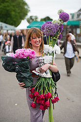 © London News Pictures. 23/05/2015. London, UK. Katie McGloughlin carrying arms full of flowers. Members of the public carry exhibitors' plants from the 2015 Chelsea Flower show, which ends today (Sat). The Royal Horticultural Society flagship flower show has been held at the Royal Hospital in Chelsea since 1913. Photo credit: Ben Cawthra/LNP