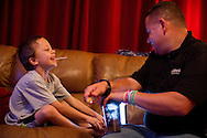 Todd Cooper and his wife, Cindy, lost their oldest child, Brianna, in a fatal crash in 2010 when she was 11 years old. Recently, their seven-year-old, Brandon, was diagnosed with chronic myeloid leukemia. During their nightly dispensing ritual, Brandon shares his enthusiasm with his father, Todd Cooper, as he gets close to beating his old time for taking his chemotherapy drug via oral syringe at home in Stuart on Sept. 25, 2014. Brandon drinks the drug in small portions, due to its taste and the nausea it can induce, but has shortened the time it takes him from over 40 minutes to under six. Todd holds a cup of apple juice, which Brandon uses to chase the medicine from the syringe, followed by a lollipop. (Xavier Mascareñas/Treasure Coast Newspapers)