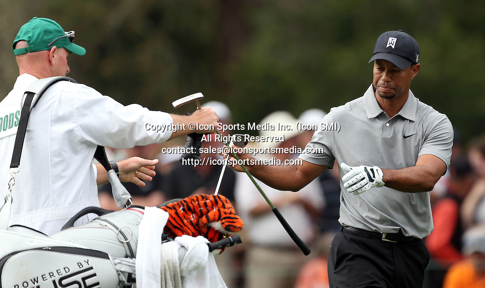 April 11, 2013 - Augusta, GA, USA - Tiger Woods exchanges clubs with caddie Joe LaCava, left, on the No. 1 fairway during the opening round of the Masters Tournament at Augusta National Golf Club in Augusta, Georgia, Thursday, April 11, 2013