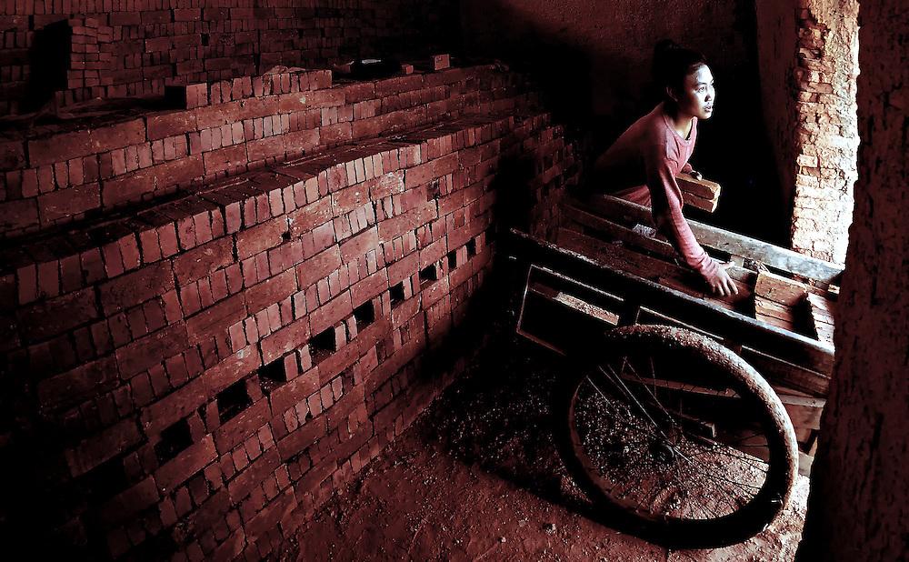 A girl loading a trolley of bricks in a kiln in Sainyabuli province, Laos.