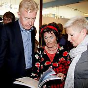 NLD/Laren/20100419 - Overhandiging boek John Kraaijkamp, Andre van Duin bekijkt samen met de ex-vrouw van John Kraaykamp Rim Sartori het ouvreboek
