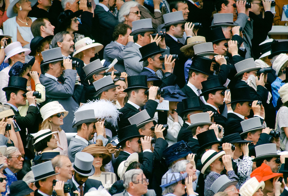 Crowds of spectactors in traditional top hats and tails using binoculars to watch the racing at Epsom Racecourse for Derby Day, UK