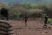 A young Pokot man walks away as a woman dances and sings his praise, after having killed a bull during an initiation ceremony to become recognised as an adult within his community, about 80 Kilometres from the town of Marigat, in Baringo County, Kenya, January 20, 2016.