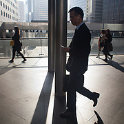 Commuters rush along in the sun and shadow on a fly-over in Central on their way to work.  7 million people live on 1,104km square, making it Hong Kong the most vertical city in the world.