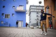 Alcuni migrnti giocano a calcio nel cortile d'ingresso delle ex palazzine olimpiche.