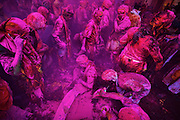 People covered with layers of color gets up, after commencing the event of Samaaj in Barsana village while celebrating Holi, the festival of colors in this small village of Mathura.<br /> <br /> People sit together and sing and abuse each other in braj language while others throw colored powder and water on them.