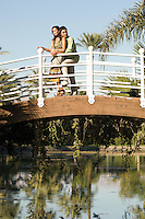 Couple embracing on bridge in park