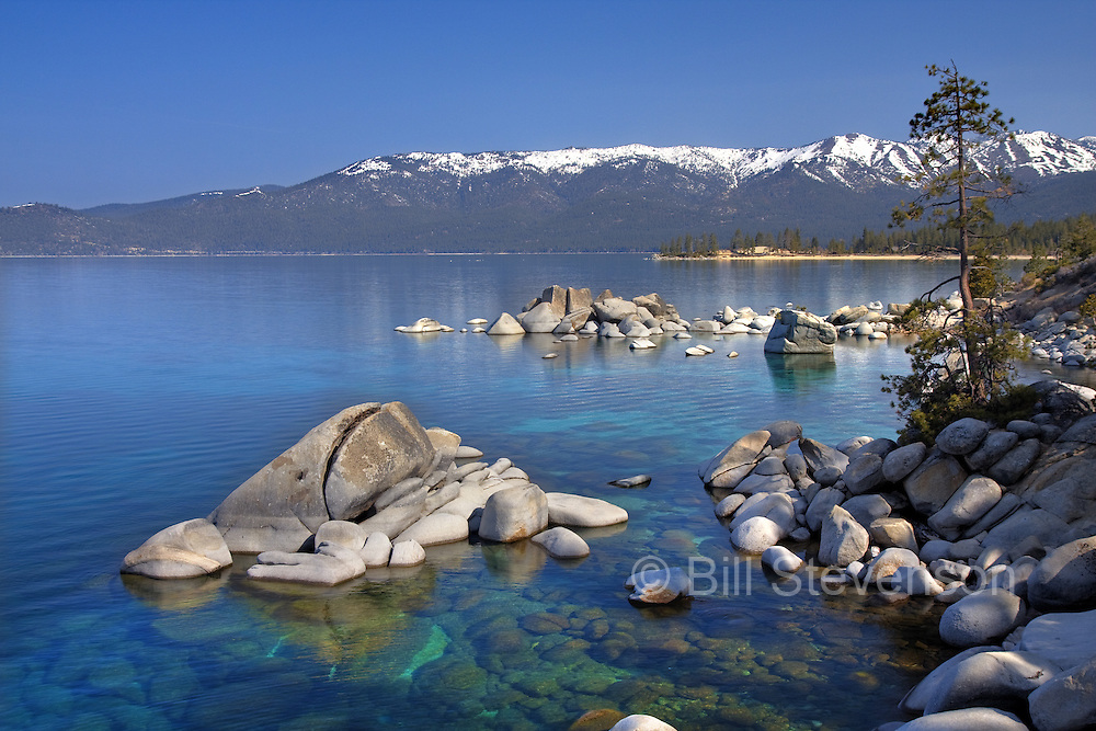 A photo of the shoreline of Lake Tahoe and its beautiful blue green water.