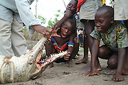 Children from Mbueca Village pose with a recently capture and killed crocodile Lake Niassa aka Lake Malawi, Niassa Province, Mozambique. Africa.