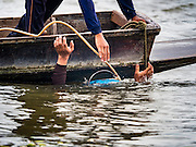 06 OCTOBER 2015 - BANGKOK, THAILAND:  A diver on a salvage diver's boat surfaces from the bottom of the Chao Phraya River in Bangkok. Divers work in two man teams on small boats in the Chao Phraya River. One person stays in the boat while the diver scours the river bottom for anything that can be salvaged and resold. The divers usually work close to shore because the center of the river is a busy commercial waterway with passenger boats and commercial freight barges passing up and down the river all day long. The Chao Phraya is a dangerous river to dive in. It's deep, has large tidal fluctuations, is fast flowing and badly polluted. The divers make money only when they sell something.    PHOTO BY JACK KURTZ