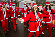 The start in teh rain - Participants of all ages don Santa suits for the London Santa Dash on Clapham Common. The event was to raise money for the Great Ormond Street Hospital (GOSH) Children's Charity and involved a 5 or 10k run.