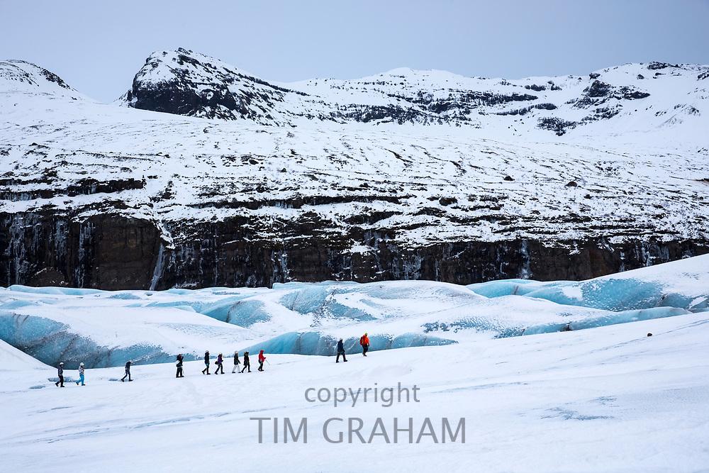 Tourists wearing protective clothing for glacier hike on Svinafellsjokull glacier an outlet glacier of Vatnajokull, South Iceland