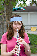 Woman age 17 warming up her oboe for the parade. MayDay Parade and Festival. Minneapolis Minnesota USA