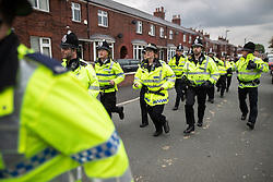 © Licensed to London News Pictures . 18/05/2019. Oldham, UK. Police run through the street after bottles, bricks and eggs are thrown by both sides at each other and fights break out . Former EDL leader Stephen Yaxley-Lennon (aka Tommy Robinson ) continues his campaign for a seat in the European Parliament representing the North West of England , by visiting Oldham . Photo credit: Joel Goodman/LNP